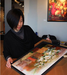 Owner Hong Zhu with one of her paintings